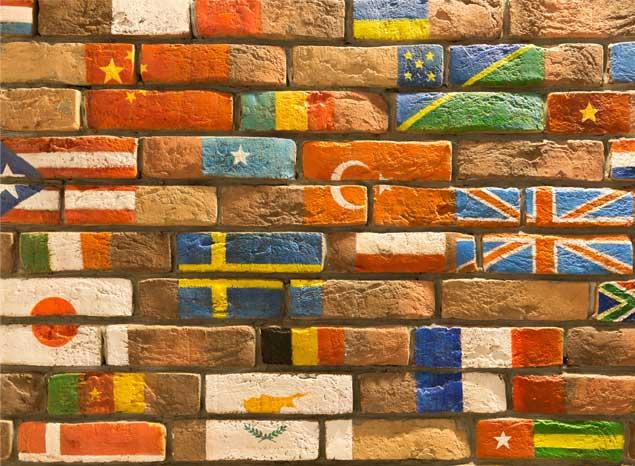 Különböző nyelveket szimbolizáló nemzeti zászlók felfestve egy barna téglafalra.