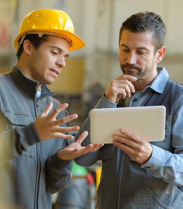 Vállalati szaknyelvi tréningen a nyelvoktató és a cég munkatársa beszélgetnek.
